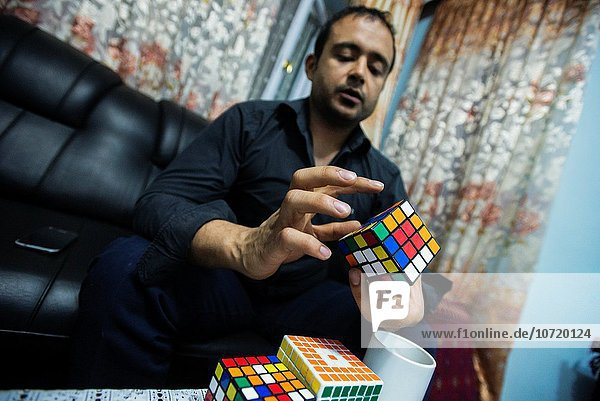 AJ Rais  head of Kabul Pressistan Media Company  combines Rubik´s Cube at his house  Kabul  Afghanistan.