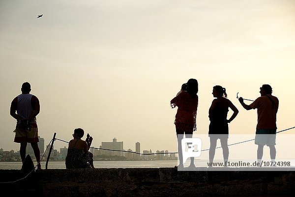 Visitiors enjoying the view of Havana's Malecón and skyline from the fort accross the bay.