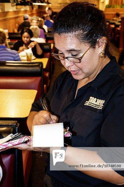 Frau Angestellter schreiben Hispanier Restaurant innerhalb Original Feinkostgeschäft Florida Gourmet Ordnung Kellnerin