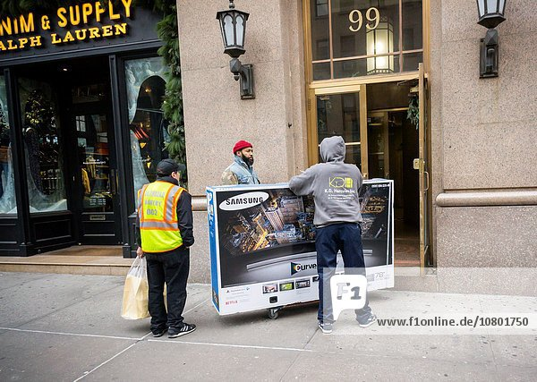 A worker attempts to delivery a humongous Samsung 4K UHD television to a building in New York. The cost of 4K televisions has come down precipitously this year making them the great hope of retailers as the hot holiday item.