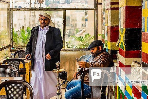 Man smoking sheesha (waterpipe)  Al-Rasheed Court Cafe (a. k. a. Eco-tourism Cafe)  Downtown Amman  Jordan.