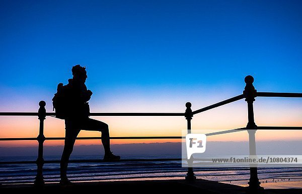 Monday 12th October 2015  Seaton Carew near Hartlepool  north east England  United Kingdom. Weather: A walker on the England Coast Path at Seaton Carew looks out over the North Sea under a clear sky 40 minutes before sunrise on a bright and chilly Monday morning on the north east coast. PICTURED: The government is putting additional funding in place over the next 5 years  to make sure that the England Coast Path  a new National Trail around all of Englandâ.s coast. is completed by 2020.
