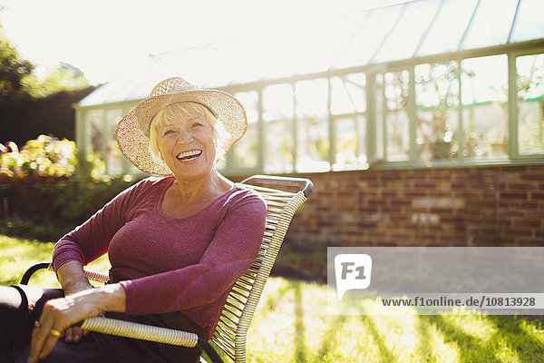 Portrait begeisterte Seniorin sitzt vor einem sonnigen Gewächshaus