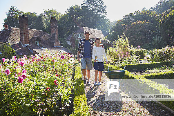 Vater und Sohn wandern im sonnigen Garten
