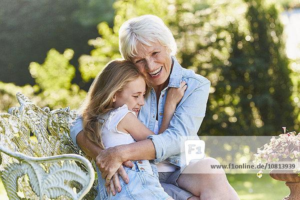 Großmutter und Enkelin umarmend auf der Gartenbank