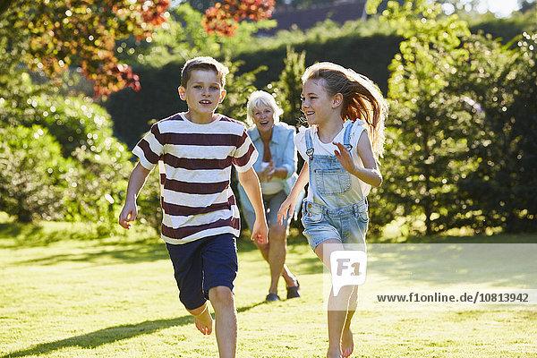 Geschwister laufen im sonnigen Garten