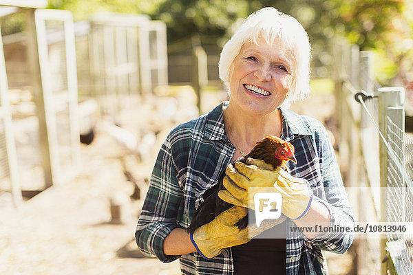 Portrait lächelnde Frau hält Huhn in der Nähe von Stallungen