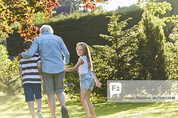 Portrait lächelndes Mädchen beim Spaziergang mit Großmutter und Bruder im Garten