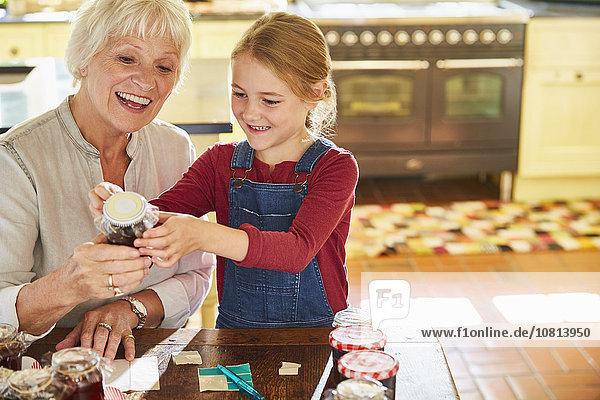 Großmutter und Enkelin etikettieren Einmachgläser in der Küche