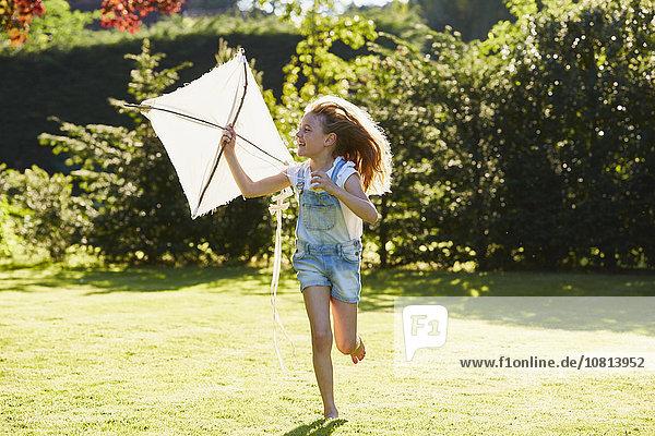Mädchen läuft mit Drachen im sonnigen Garten