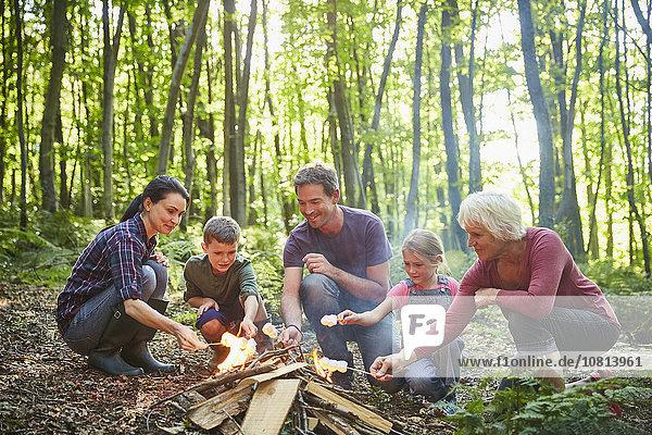 Mehrgenerationen-Familienbraten von Marshmallows am Lagerfeuer im Wald