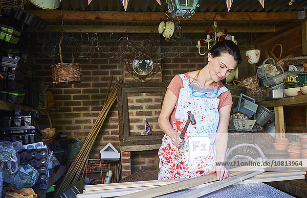 Frau hämmert Holzbretter in der Werkstatt