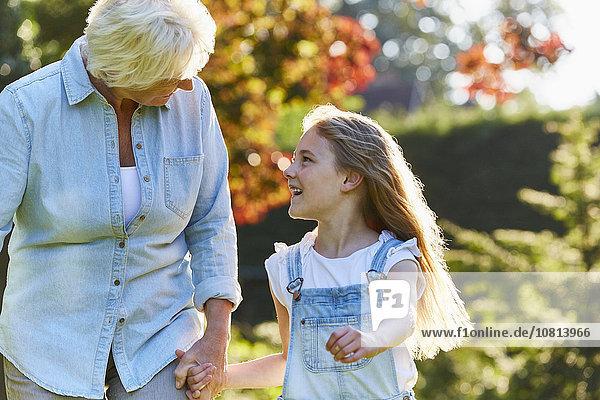 Großmutter und Enkelin beim Händchenhalten und Spazierengehen im sonnigen Garten
