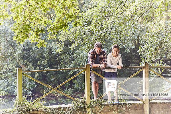 Vater und Sohn auf Fußgängerbrücke im Park mit Bäumen