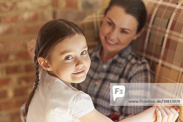 Porträt lächelndes Mädchen hält sich an den Händen der Mutter