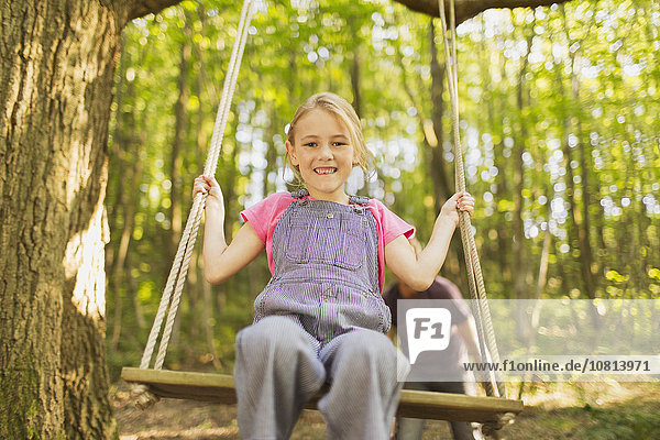 Portrait lächelndes Mädchen am Seil schwingend im Wald