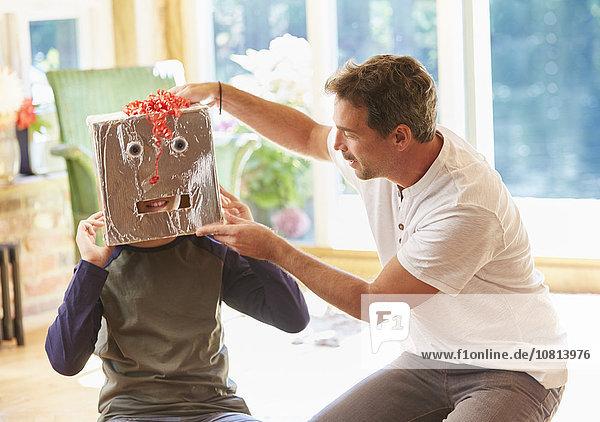 Vater platziert Robotermaske auf Sohn