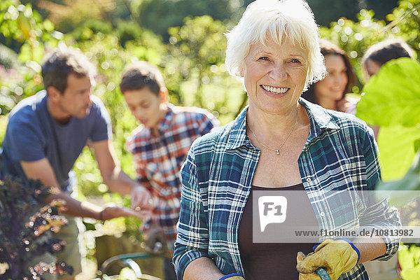 Portrait lächelnde Seniorin im sonnigen Garten mit Familie