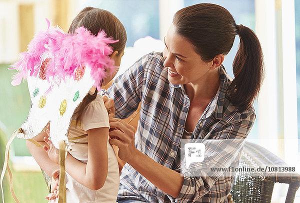 Mutter montiert Flügel auf Tochter