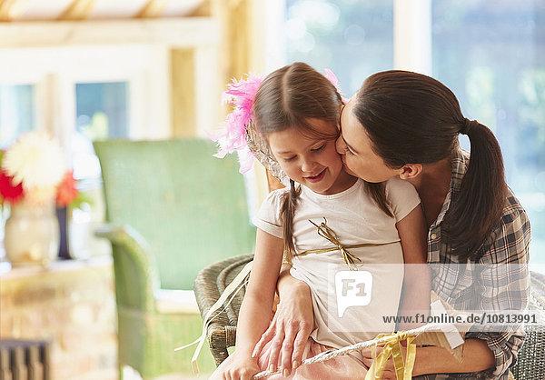 Mutter, die die Wange ihrer Tochter küsst.