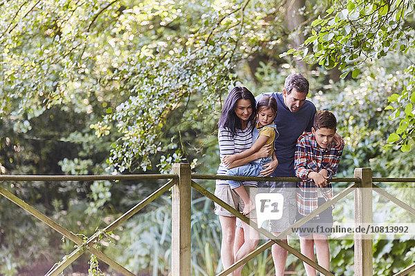 Familie steht auf Fußgängerbrücke im Park mit Bäumen