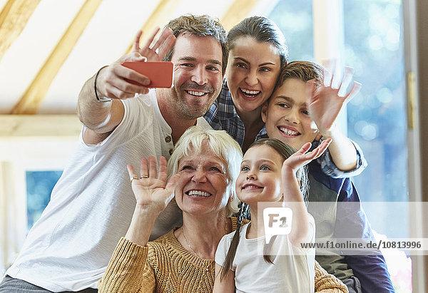 Mehrgenerationen-Familie winkt und nimmt Selfie