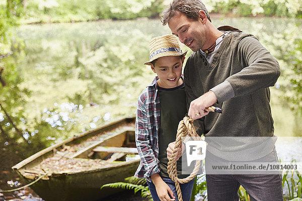 Vater lehrt den Sohn, wie man einen Seilknoten bindet.