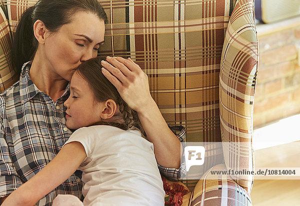 Zarte Mutter kuschelt schlafende Tochter im Sessel