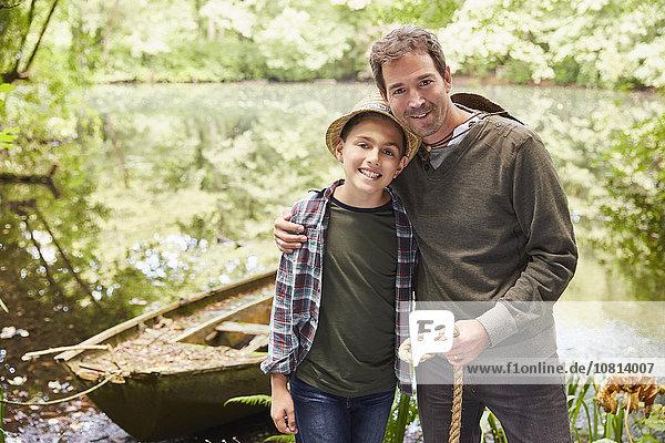 Portrait Vater und Sohn mit Boot am Teich