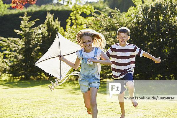 Geschwister laufen mit Drachen im sonnigen Garten