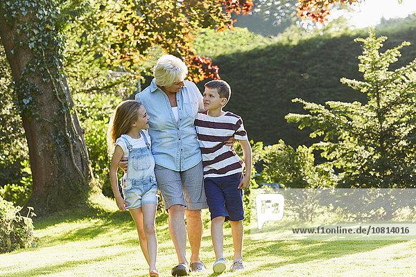 Großmutter und Enkelkinder wandern im sonnigen Garten