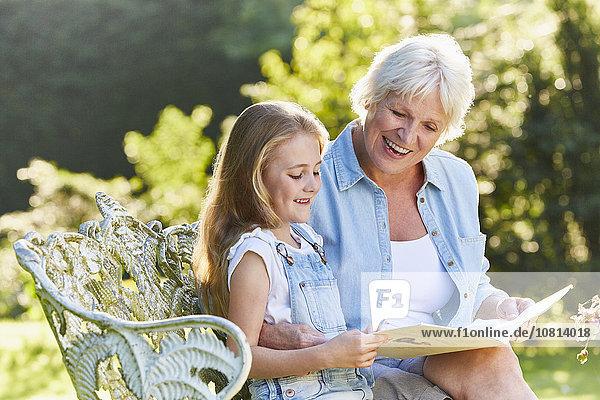 Großmutter beim Lesen mit Enkelin auf der Gartenbank