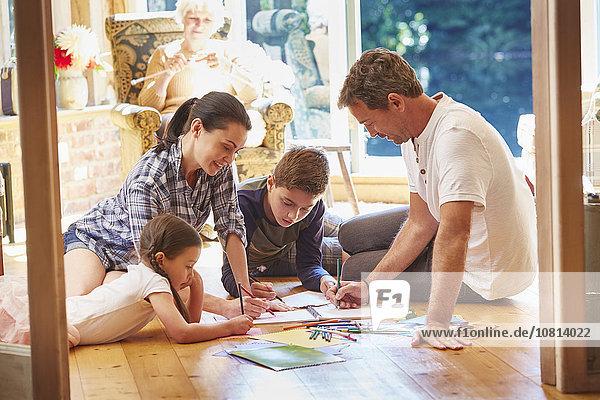 Familienzeichnung und Farbgebung auf dem Boden im Wohnzimmer