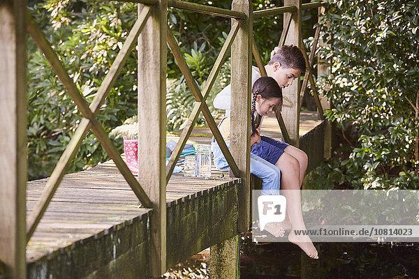 Bruder und Schwester baumeln barfuß über den Steg.