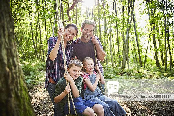 Portrait lächelnde Familie bei Seilschaukel im Wald