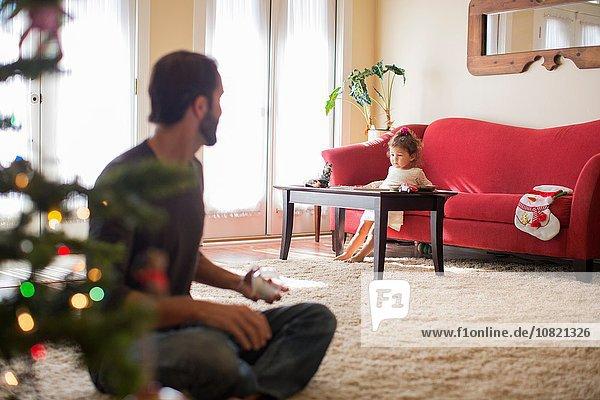 Mädchen auf Sofa sitzend  Vater im Vordergrund