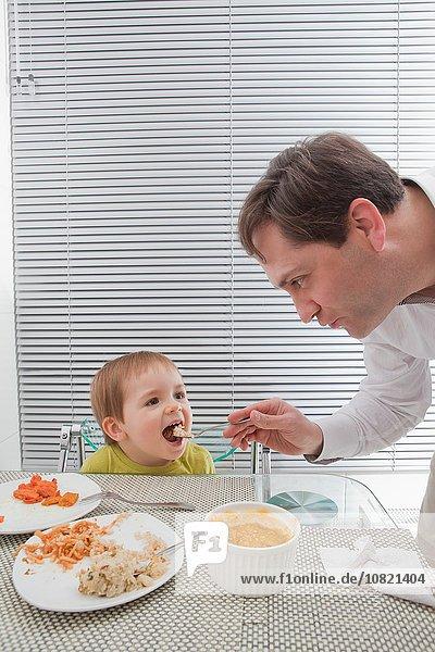 Vater füttert Sohn am Esstisch
