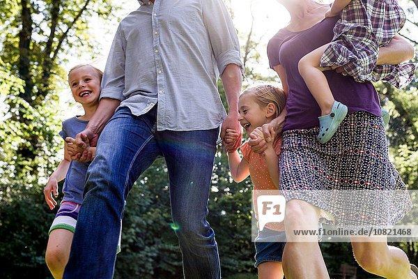 Schnappschuss von Eltern und drei jungen Töchtern  die im Park rennen.