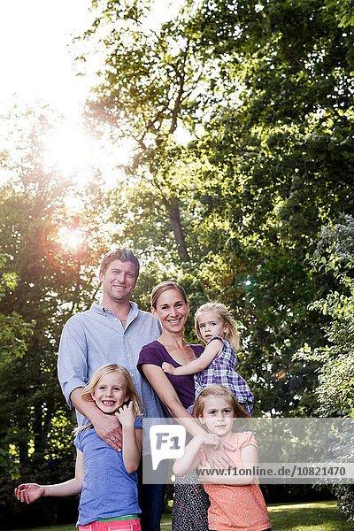 Porträt von Eltern und drei jungen Töchtern im sonnenbeschienenen Park