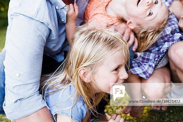 Schnappschuss von Eltern und drei jungen Töchtern im Park