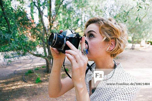 Mittlere erwachsene Frau beim Fotografieren im Park