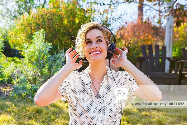Mittlere erwachsene Frau mit Kopfhörer  draußen  lächelnd