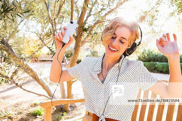 Mittlere erwachsene Frau auf der Bank sitzend  Kopfhörer tragend  Smartphone haltend  tanzend