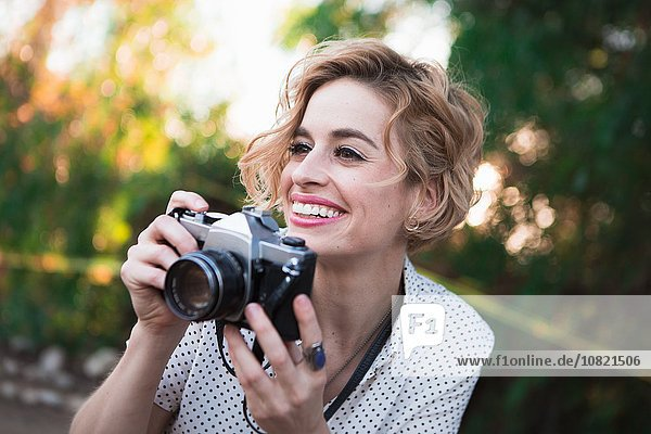 Mid adult woman taking photographs,  outdoors,  smiling