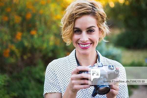 Porträt einer mittleren erwachsenen Frau mit Spiegelreflexkamera  lächelnd