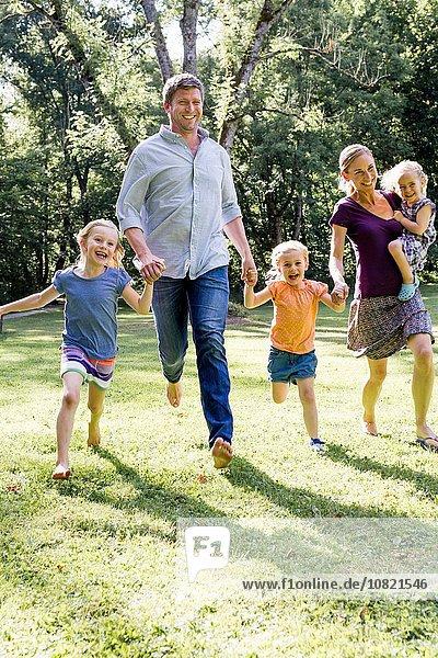 Paar  das mit drei Töchtern im Park läuft und Händchen hält.