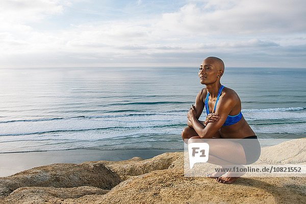 Young woman crouching on rocks beside sea