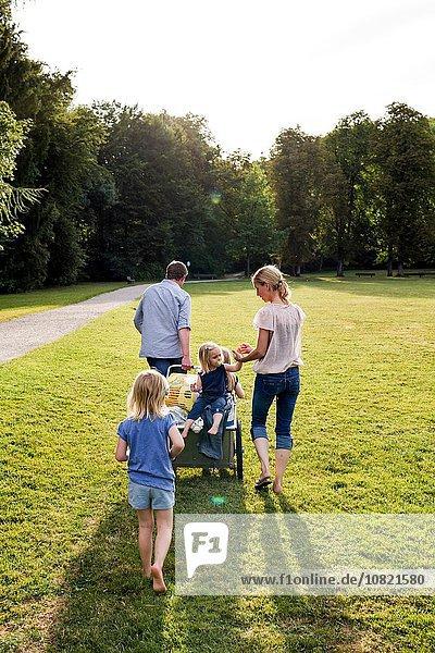Rückansicht der Eltern und drei Mädchen beim Spaziergang im Park
