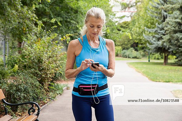 Mature woman choosing smartphone music whilst training in park