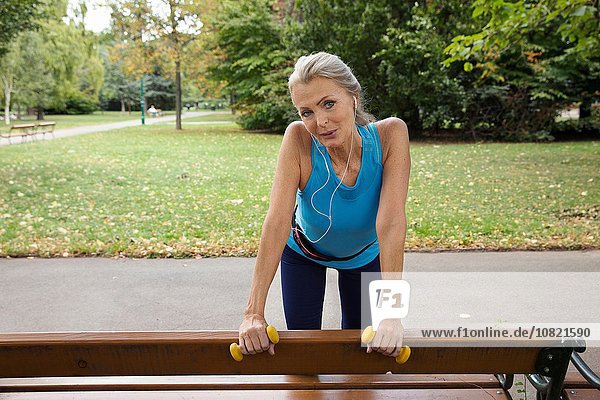 Portrait of mature woman at park bench whilst training in park